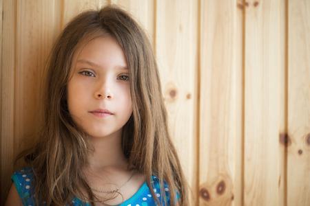 petite fille avec robe: Petite fille calme dans robe bleue sur fond de bois