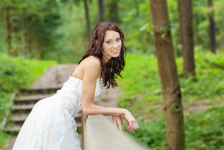 Young beautiful bride in white wedding dress standing on bridge over stream in summer park. photo