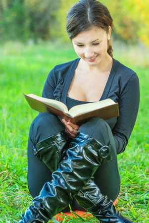 grass plot: Young beautiful woman in black jacket reads book against autumn nature.