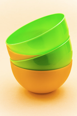 Four plastic plates yellow and green on table. photo