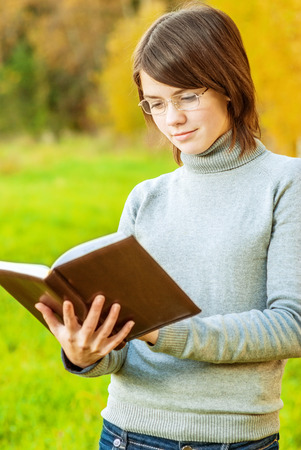 grass plot: Young girl with book and glasses has reflected against an autumn field.
