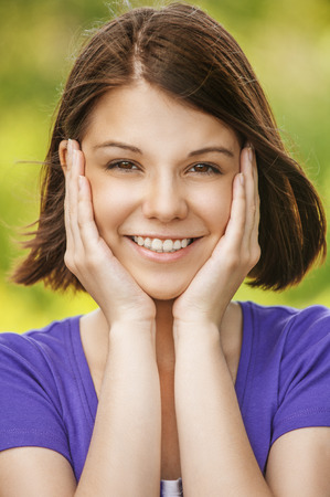 Close-up portrait of young beautiful smiling woman propping up her face in front of summer green park.