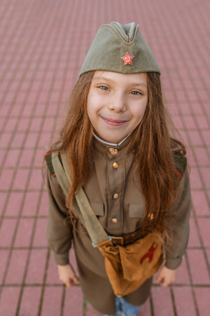 female soldier: Little beautiful smiling girl in Soviet military uniforms.