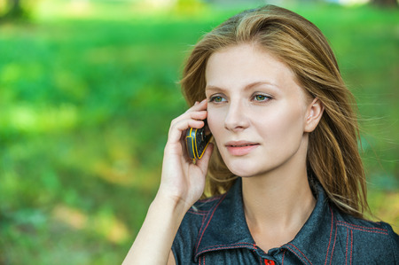 naturally: Young beautiful woman talks by mobile phone, on green background. Stock Photo
