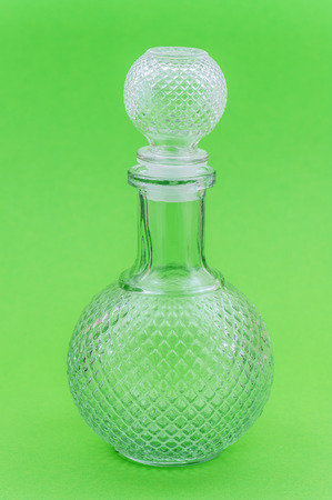 decanter: Beautiful crystal decanter stands on green background. Stock Photo