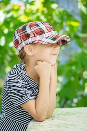 aslant: Little girl in hat of park in summer.