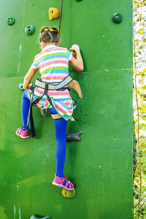 Little girl talking trains on climbing wall in summer city park. photo