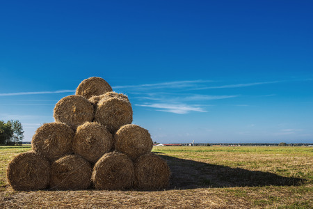 Thunderclouds hang over haystack in autumn field. photo