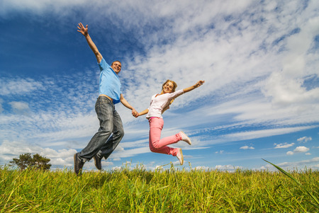 skip: Young couple jumping on background of blue sky. Stock Photo