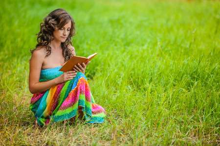 ravishing: Portrait of young attractive beautiful dark-haired curly woman holding book at summer green park.