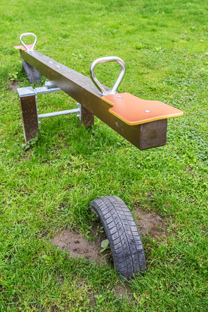 Seesaw (also known as teeter-totter or teeterboard) is a long narrow board pivoted in the middle so that, as one end goes up, the other goes down. photo