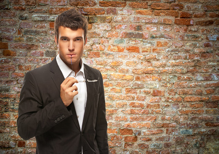 portrait young businessman thinking and keeps the glasses to his mouth against background of brick wall photo