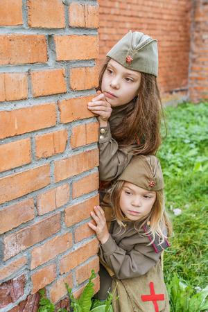 female soldier: Little beautiful girls in Soviet military uniforms. Stock Photo