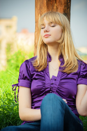 uncombed: Beautiful blonde sits about an old wooden column. Stock Photo