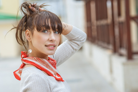 kerchief: Beautiful girl with kerchief on neck against wooden handrail. Stock Photo