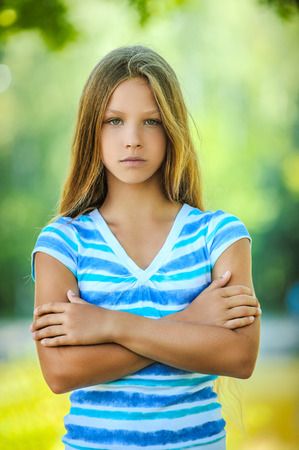 moody: Beautiful sad teenage girl in blue blouse, against green of summer park.