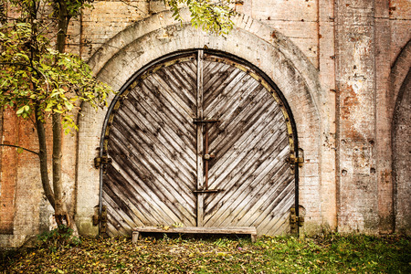Arched wooden garage doors in a old house. photo