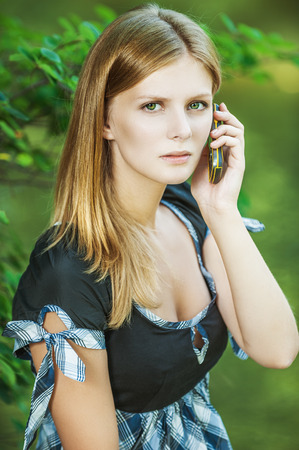russian woman: Young beautiful woman talks by mobile phone, on green background. Stock Photo