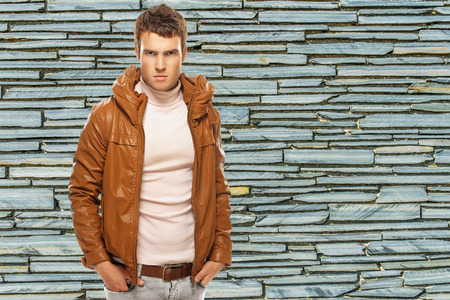 Gloomy young man in brown jacket, on stone wall background. photo