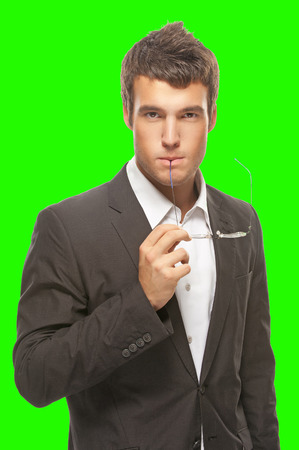portrait young businessman thinking and keeps the glasses to his mouth isolated on green background photo