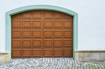 garage on house: Arched wooden garage doors in a modern house.
