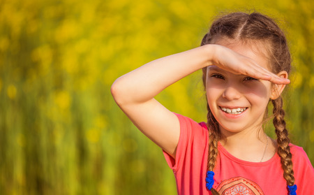 shielding: Little smiling beautiful girl closes her eyes from the sun, on a background of green summer city park. Stock Photo