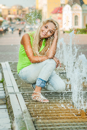 waterfall in the city: Smiles girl holds hands over fountain and laughs.