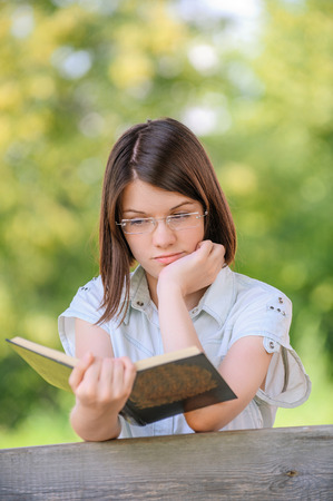 engaging: Portrait of young beautiful serious cute dark-haired girl reading engaging book and wearing white chemise at summer green park.
