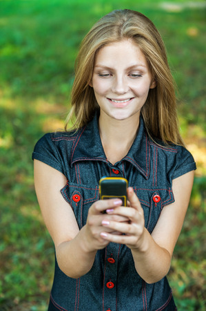 surprise face: Beautiful young woman looking at mobile phone on green background Stock Photo