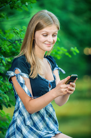 adult intercourse: Beautiful young woman looking at mobile phone on green background Stock Photo