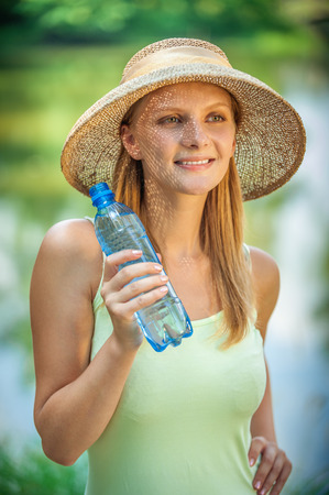 freshening: Young beautiful girl in straw hat against lake in city park drinks water from plastic bottle. Stock Photo