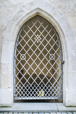 rejas de hierro: Ventana en un edificio antiguo europeo con rejas de hierro forjado.