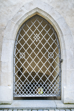 wrought iron: Window on an old European building with wrought iron bars.