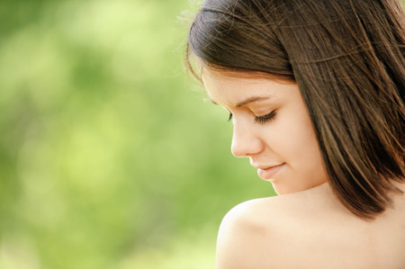 appealing: Close-up portrait of young appealing brunette woman at summer green park. Stock Photo