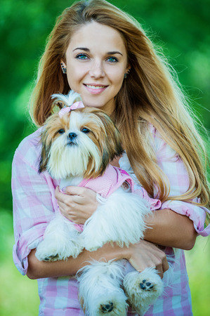 allegiance: Portrait of pretty, young, smiling woman holding small fluffy dog, against background of summer green park