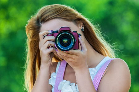 shootting: Portrait of beautiful smiling young woman with camera, against green of summer park.