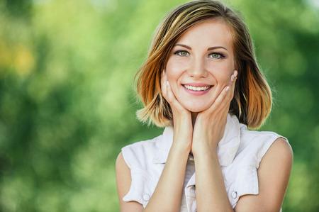 夏の公園の緑との美しい若い女性のクローズ アップの笑顔の肖像画。
