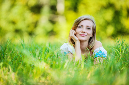 ravishing: Portrait of young beautiful brunette woman lying on grass and propping up her face at summer green park.