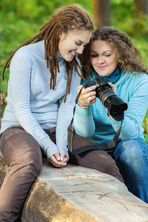 fair complexion: Girlfriends look through finished shooting pictures on camera. Stock Photo