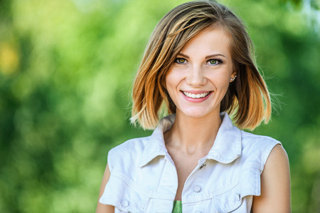 ?  ?    ?  ?    ?  ?    ?  smiling: Retrato de la sonrisa hermosa mujer joven de cerca, contra el verde del parque de verano. Foto de archivo