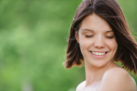 young naked girl: Close-up portrait of young pleasant dark-haired woman at summer green park. Stock Photo