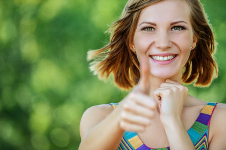 Beautiful young woman close-up in colorful dress, against green of summer park. Stock Photo