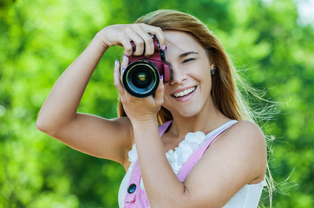 Portrait of beautiful smiling young woman with camera, against green of summer park.