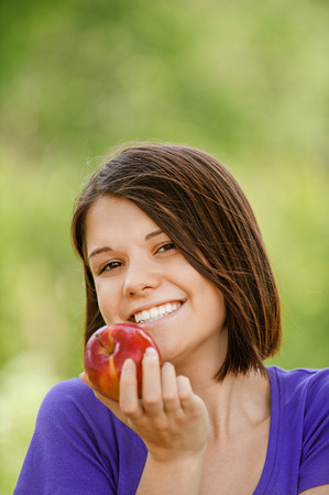 Portrait of young cheerful attractive smiling woman eating red ripe apple at summer green park. photo