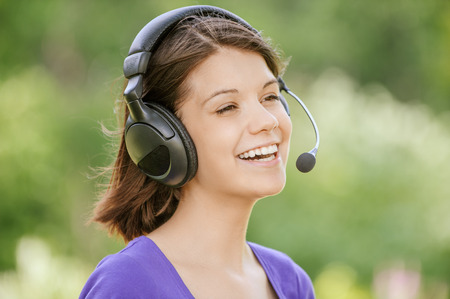 Portrait of young smiling woman wearing earphones with microphone standing at summer green park. photo