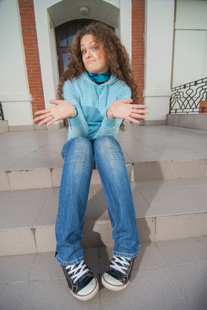 fair complexion: Curly beautiful woman sits on steps.