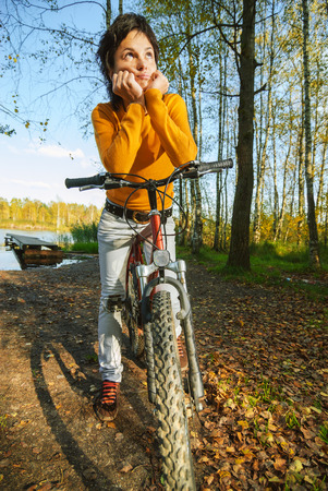 Beautiful girl riding bicycle against autumn nature. photo
