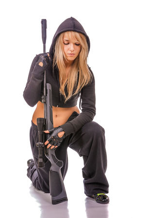 fair complexion: Young beautiful woman in black clothes and with rifle in hands.