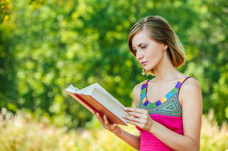 autodidact: serious young beautiful short-haired woman holding red book looking sideways background summer green park