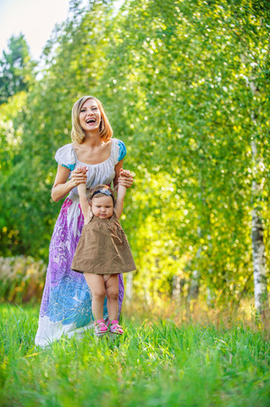 beautiful young woman long dress plays child field background summer meadow green trees photo